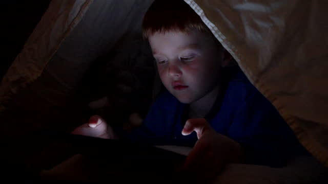 Young Boy Using tech or watching a film on digital tablet in the darkness of a camp