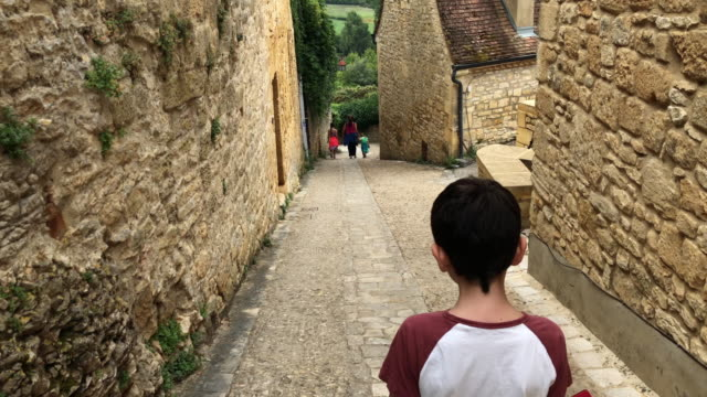 Young boy walking through the old streets of Beynac, France video