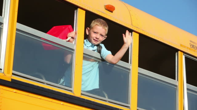 young boy waves out window of school bus - school buses stock videos and b-roll footage