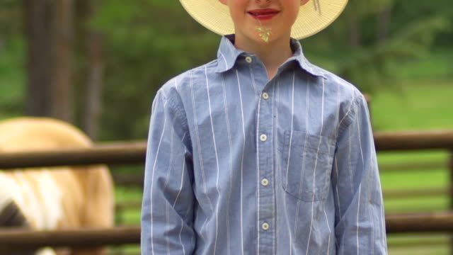 A young boy with a cowboy hat looks into the camera