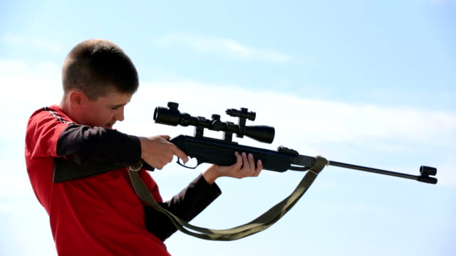 Young boy with air rifle shooting video