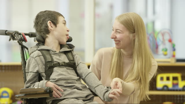 Young Boy with Disability Smiles and Laughs with Caregiver A female caregiver smiles and laughs while holding the hand of a young boy with a disability who is in a wheelchair. disability stock videos & royalty-free footage