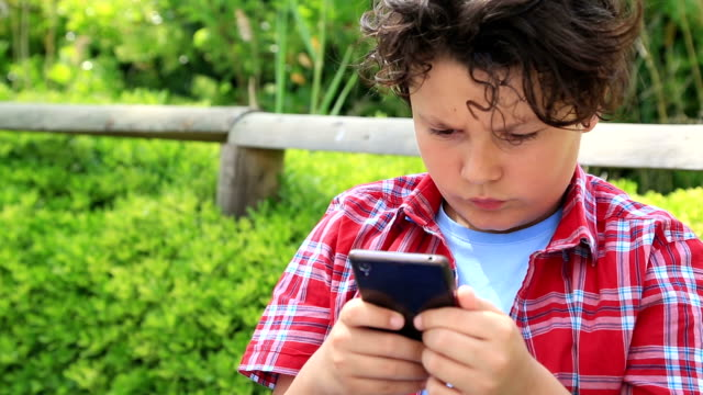 Young boy with smartphone Young boy  playing  with mobile smartphone at the garden. Smartphone addiction one boy only stock videos & royalty-free footage