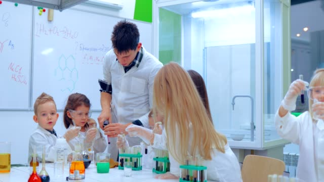 Young boys and girls is making chemistry experiments. Teacher and children in chemistry class video