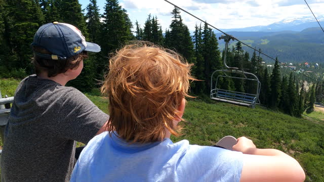 Young boys ride chairlift above Mt Washington, BC