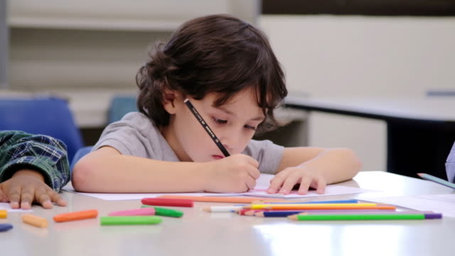 Young boys sitting drawing coloring video