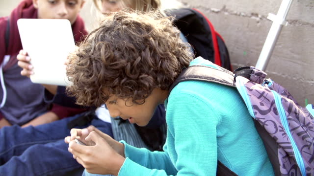 Young Boys Using Digital Tablets And Mobile Phones In Park Group of young boys sitting by wall in playground playing games digital tablet and mobile phone.Shot on Sony FS700 at frame rate of 25fps one boy only stock videos & royalty-free footage