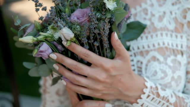 Young bride is holding bouquet of flowers in hands standing indoors video