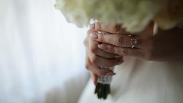 窓の近くのホテルの部屋に立っている間、結婚式のブーケを持つ指にダイヤモンドの指輪を持つ若い花嫁 - 結婚式点の映像素材/bロール