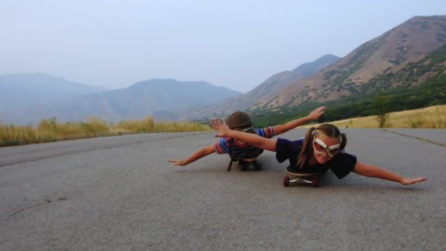Young Brother and Sister Racing on Skateboards