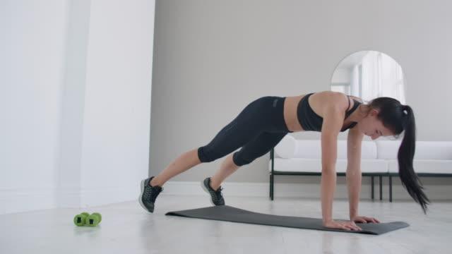 ung brunett gör cardio workout för abs muskler - hemmaträning bildbanksvideor och videomaterial från bakom kulisserna