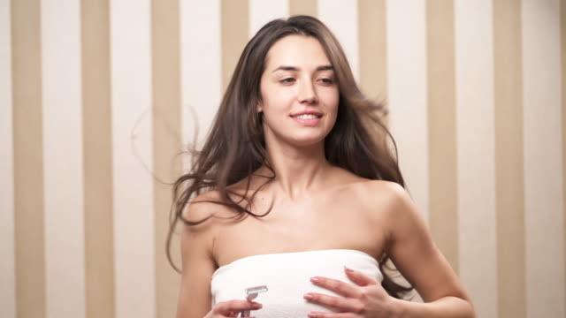A young brunette girl emerges in the blank shot. Smiling and looking happy. Holding a razor and imitating shaving her armpit video
