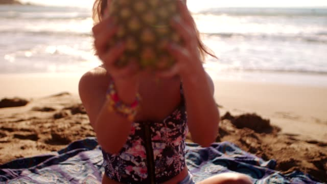 Young brunette girl with pineapple at a beach at summer video
