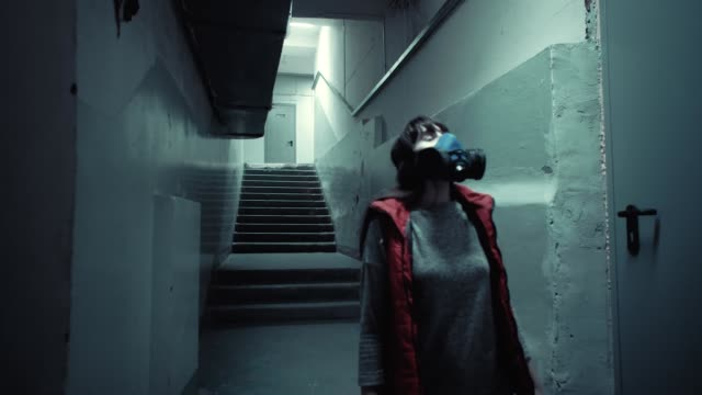 A young brunette in blue protective goes down an old dark staircase. video