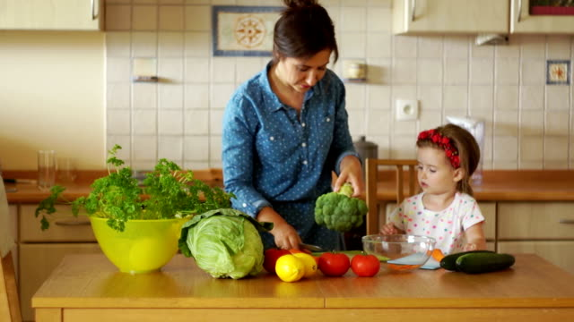 vídeos de stock e filmes b-roll de young brunette is cutting vegetables in the kitchen. she took broccoli and carrots. her little daughter helps her mother, she participates in cooking dinner. parenting. healthy food - saladeira