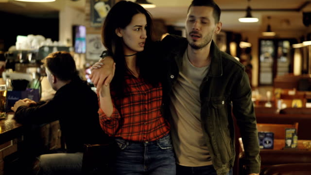Young brunette is leading her drunk husband out of bar. Unshaven handsome young man is talking to his upset wife trying to explain himself. Alcoholism ruining family concept.