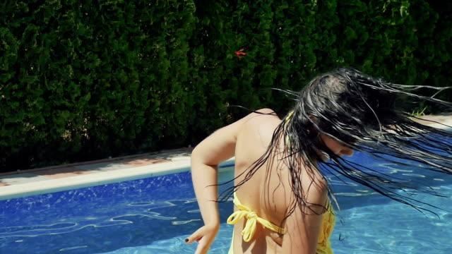 vidéos et rushes de jeune brunette déplace les cheveux mouillés, posant pour la caméra dans la piscine - rouge à lèvres rouge