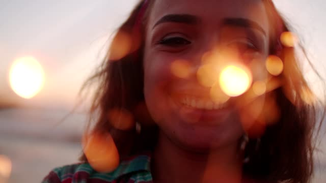Young brunette with fireworks on a beach at sunset video