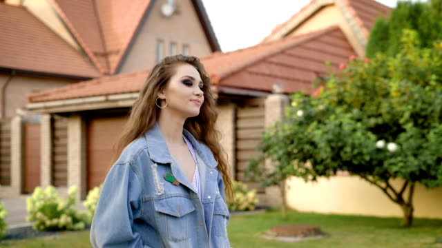 Young brunette with heavy makeup wearing denim and posing at street of countryside Young brunette with heavy makeup wearing denim and posing at street of countryside. Model with strong makeup looking away on background of countryside charming stock videos & royalty-free footage