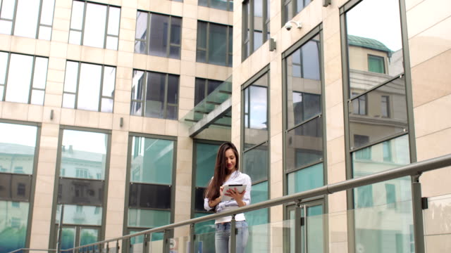 Young brunette with long hair with tablet in city. Sexy girl with long hair reading digital tablet in the background of office building. dormir stock videos & royalty-free footage