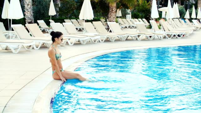 ung brunett kvinna i bikini och solglasögon som sitter på tedge av poolen och gör plaska i solig sommardag - tjänstekvinna bildbanksvideor och videomaterial från bakom kulisserna