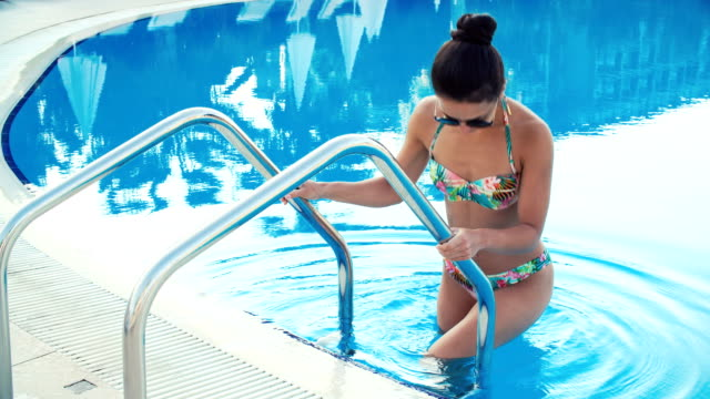 young brunette woman in bikini and sunglasses walks into swimming pool and swims on Sunny summer day young brunette woman in bikini and sunglasses walks into the swimming pool and swims on a Sunny summer day competition group stock videos & royalty-free footage