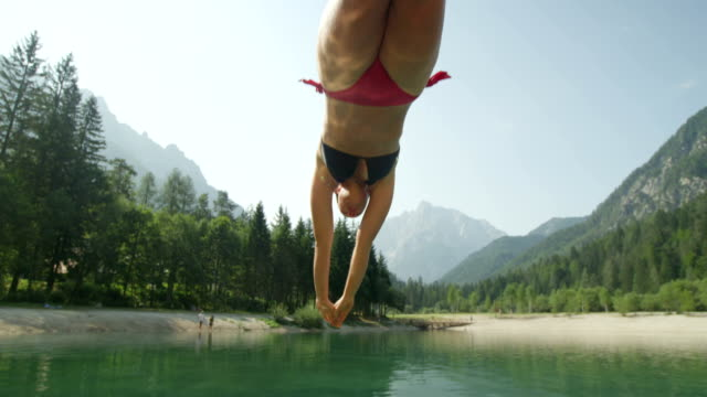 SLOW MOTION CLOSE UP: Young brunette woman in bikini jumping over the camera and diving into the beautiful mountain lake in sunny summer video