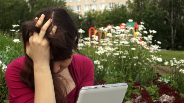 Young brunette woman in depression using a tablet next to daisies in the park. video