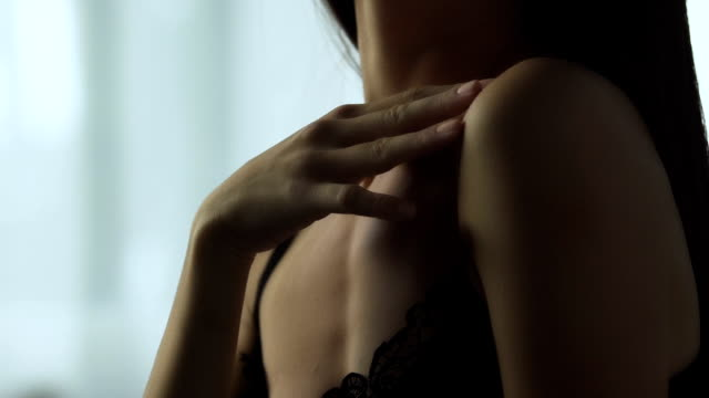 Young brunette woman in lingerie gently touching soft skin, body care products video