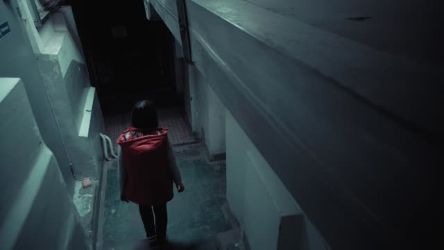 Young brunette woman in red sleeveless jacket descends down long stairs in dark. video