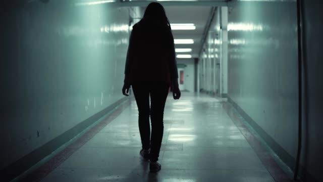 Young brunette woman in red sleeveless jacket is walking long dark corridor video