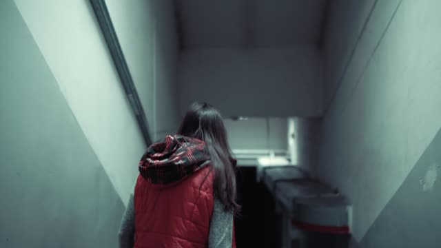 Young brunette woman in red sleeveless jacket is walking long stairs in dark. video