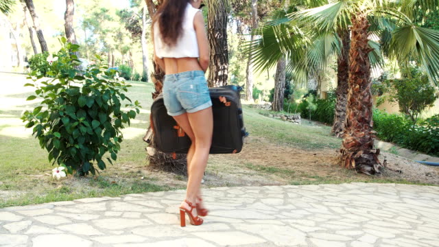 young brunette woman in shorts, sunglasses and heels carries suitcase between trees in summer. vacation video