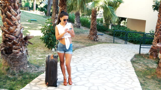 young brunette woman in shorts, sunglasses and heels with suitcase talking on phone between palm trees in summer. video