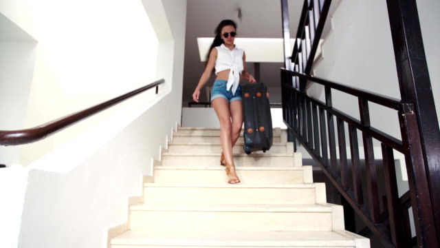 young brunette woman in shorts, sunglasses with suitcase down stairs to hotel in summer. holiday and vacation video