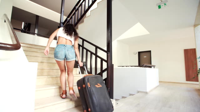 young brunette woman in shorts, sunglasses with suitcase up stairs at hotel in summer. holiday and vacation video