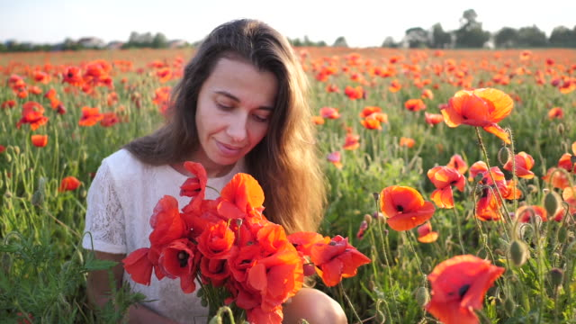 Young brunette woman in white dress stands in the middle of the field of poppies. Charming lady with incredible smile with bouquet of poppies in hands. Slow motion Full HD