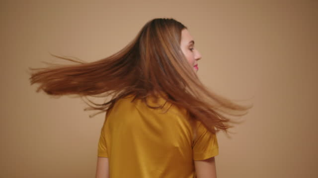 Young brunette woman in yellow t shirt playing with long hair isolated on beige background Young brunette woman in yellow t shirt playing with long hair isolated on beige background. human hair stock videos & royalty-free footage