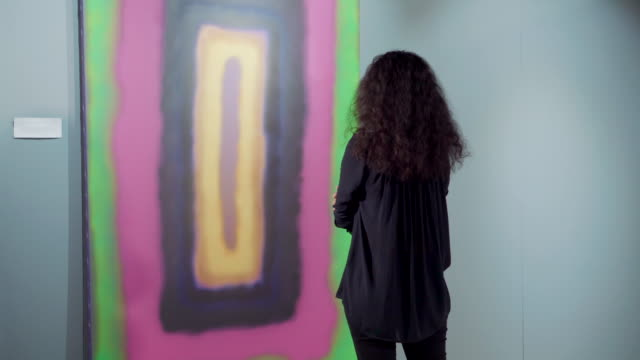 Young brunette woman is considering bright abstract picture of modern artist