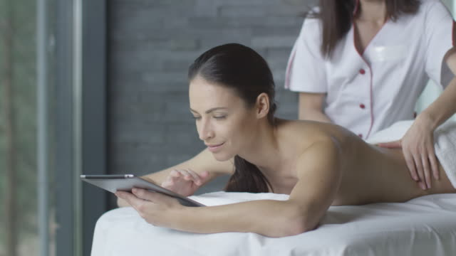Young brunette woman is using a tablet during a relaxing massage in wellness center. video