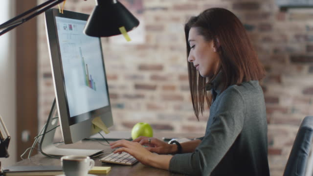 young brunette woman is working on a charts in front of a monitor in a loft. - scrivania video stock e b–roll