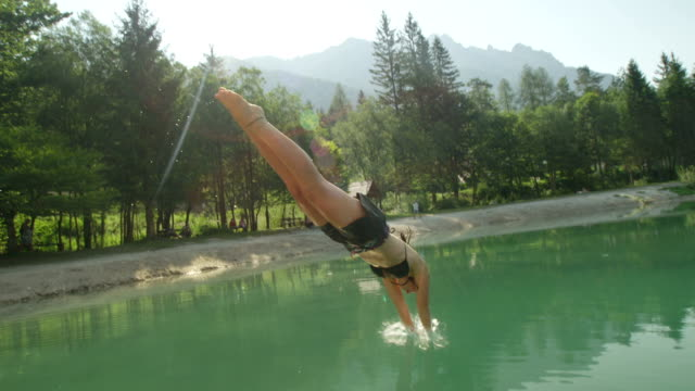 SLOW MOTION: Young brunette woman jumping over the sun and diving into the beautiful mountain lake in sunny summer video