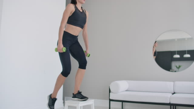A young brunette woman performs concentrated pacing on a chair in a bright interior apartment with dumbbells in her hands