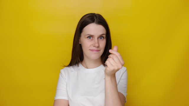 young brunette woman showing money gesture, having cunning plan for earnings big income, looking at camera smiling slyly, wears t-shirt, asking cash allowance, isolated on yellow studio background - avidità video stock e b–roll