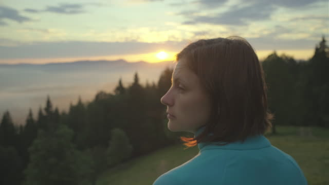 Young brunette woman standing and watching the sunrise in mountains. Lady looks at beautiful scenery early in the morning.