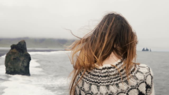 Young brunette woman standing on the shore of the sea and looking on troll toes sight in Iceland, hair waving on wind video