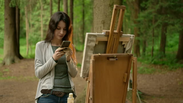Young brunette woman texting in her smartphone about her landscape artwork