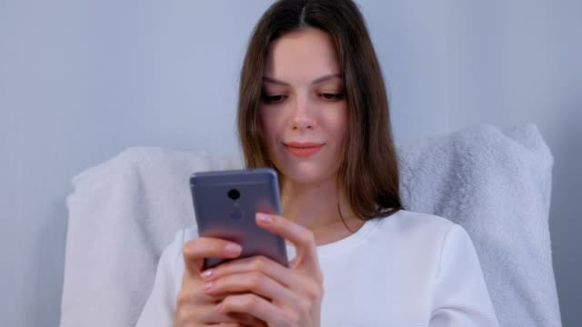 Young brunette woman types a message on a mobile phone. video