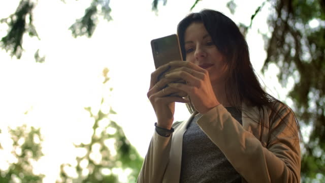 Young brunette woman typing messages in public chat in social network outdoor in the forest