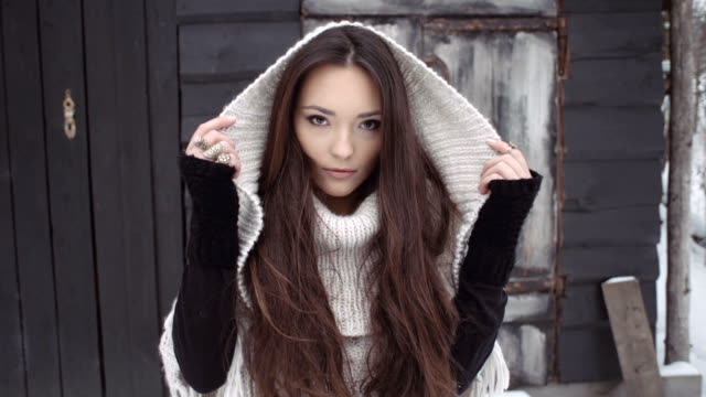 Young brunette woman wearing knitted sweater standing by the wooden house. video